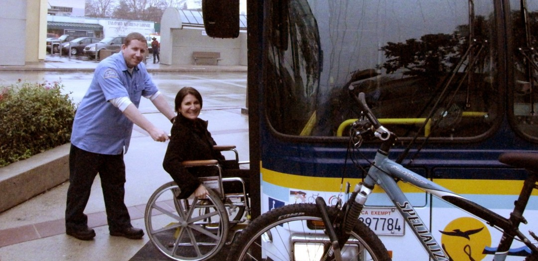 bus driver helps a woman with a wheelchair board the bus