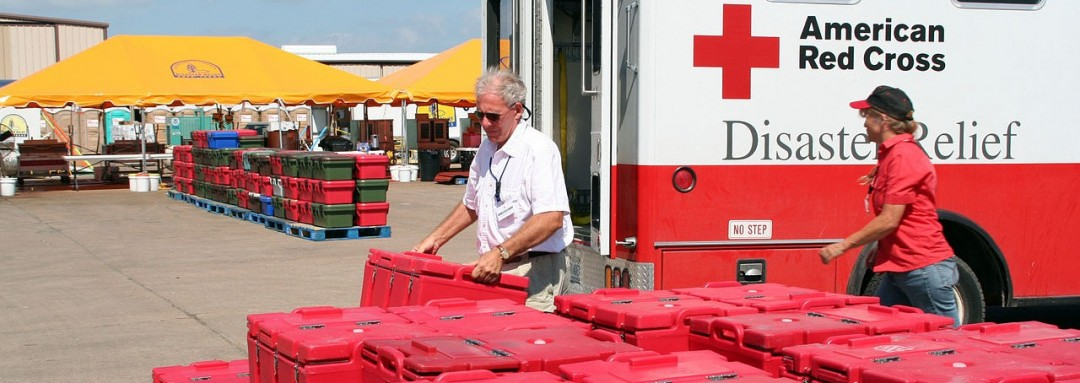 Red Cross staff in front of a Red Cross ambulance, red plastic food containers in foreground