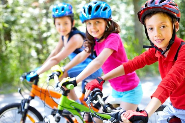 Three kids on bikes wearing helmets and colorful gear