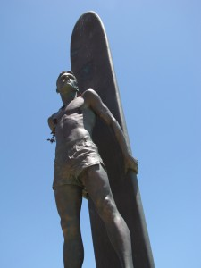 Surfer statue on West Cliff Dr., Santa Cruz against clear blue sky