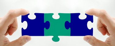 Photo of person holding three interlocking puzzle pieces