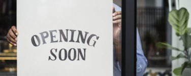 man posting opening soon sign in business storefront window